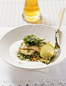 Steamed huchen fillet with stinging nettles on a bed of barley