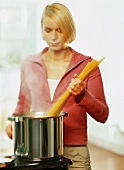 A young woman cooking spaghetti