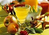 Stillleben mit Obstsaft, Obst, Gemüse und Kräutern