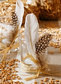 Table decoration: grains of corn and glasses with feathers