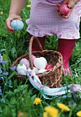 A girl standing behind a basket of Easter eggs