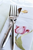 Cutlery and a napkin with a flower motif