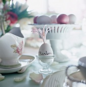 A breakfast egg as a place card on a table laid for Easter Day
