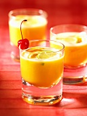 Orange drinks with cocktail cherries