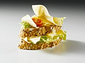 Slices of bread topped with cheese, lettuce and tomato
