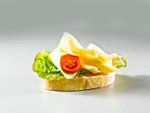 A slice of white bread topped with lettuce, cheese and tomato