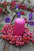 A candle with a wreath of spindle flowers