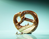 Miniature figures having a picnic on a pretzel