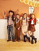 Vier Kinder, als Indianer und Cowboys verkleidet