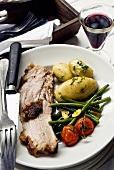 Roast pork with potatoes and a side of vegetables