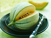A sliced Cavaillon melon, on a plate with a fork