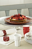 A berry tart on a table with napkins, plates and beakers