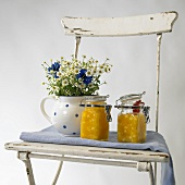 Pineapple jam and a bunch of meadow flowers on a garden chair