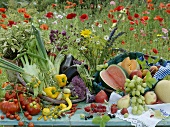 An arrangement of vegetables and fruit with a poppy field in the background
