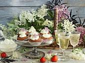 An arrangement of elderflower cakes, elderflower wine and elderflowers