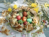 An arrangement of coloured eggs, sugar eggs, Easter bunny bread and narcicus