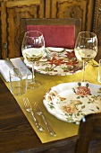 A table laid for two people with white wine