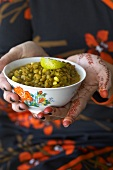 Henna-painted hands holding a bowl of lentils