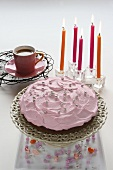 Raspberry cream cake with silver balls with candles and coffee in the background