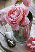 A pink faux rose and a crocheted flower as table decoration