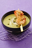 Pea cream soup with skewered prawns