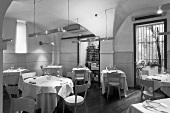 A black and white photo of a designer restaurant with a vaulted ceiling