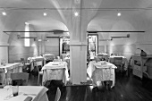 A black and white photo of a designer restaurant with a vaulted ceiling and halogen lights