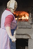 Countrywoman putting bread into a wood-fired oven