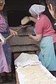 Bäuerinnen legen ungebackene Brote in alten Steinofen