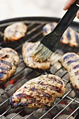 Chicken breasts on barbecue being brushed with marinade