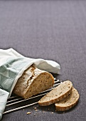Walnut bread on a rack with tea towel