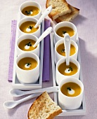 Cream of pumpkin soup in several small bowls