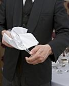 Waiter polishing wine glass