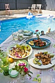 Assorted barbecued kebabs and salad on a table by a pool