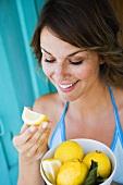 Woman holding a bowl of fresh lemons