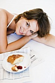 Young woman lying beside plate with croissant and jam