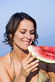Young woman eating a slice of watermelon out of doors