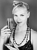 Junge Frau hält ein Glas Champagner