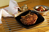 Beef steak in a grill pan with pepper and cucumber salad