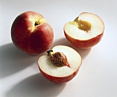 Whole and halved peach (variety: Fidelia)