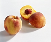 Whole and halved peach (variety: Hale)