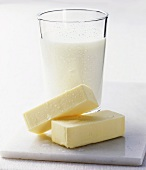 A glass of buttermilk with pieces of butter in front