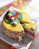 Child's birthday cake with marzipan and coloured sprinkles