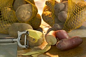 Potatoes in nets and with potato peeler