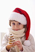 Girl in Father Christmas hat holding biscuit Christmas tree