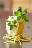 Lemon, partly peeled, lemon peel and oregano