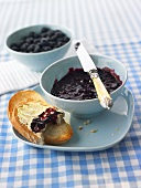 Blueberry jam in a small bowl and on bread