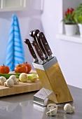 Knife in knife block, vegetables in background