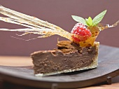 Piece of chocolate tart with caramel fan and raspberry