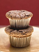 Two chocolate muffins, one on top of the other